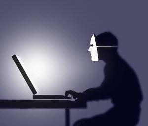 Man wearing mask using computer