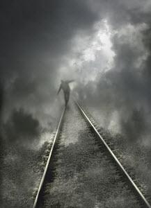 Businessman balancing on railway line