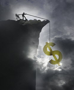 Businessman and businesswoman rescuing dollar sign on rope over edge of cliff