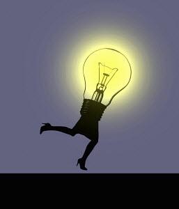 Illuminated light bulb running with woman's legs