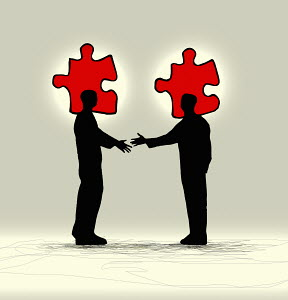 Businessmen shaking hands with matching jigsaw puzzle pieces