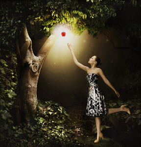 Woman reaching for glowing apple hanging from tree in woods
