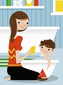 Mother bathing son in baby bathtub