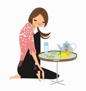 Woman enjoying ginger and lemon tea at small table