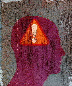 Exclamation point warning sign inside of silhouette of man's head
