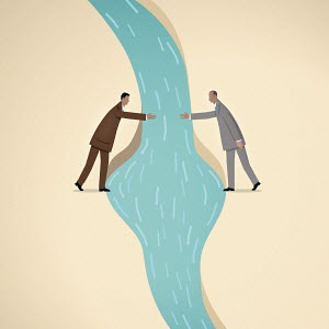 Businessmen reaching to shake hands over river