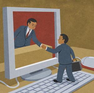 Businessmen shaking hands through computer monitor