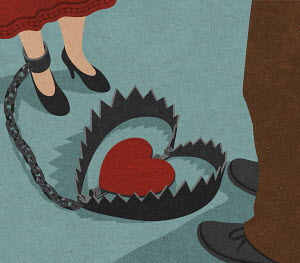 Man standing next to woman shackled to heart shaped bear trap