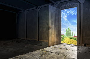 Unlocked door in gloomy room opening to bright yellow brick road