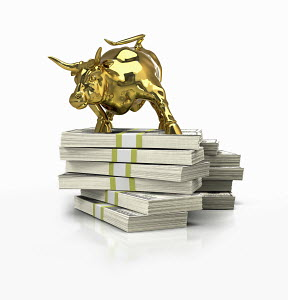 Golden bull on top of stack of one hundred dollar notes