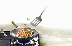 Spatula stirring stir fry vegetables in wok on gas stove