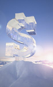 Frozen dollar sign on top of mountain peak in snowy landscape at sunrise