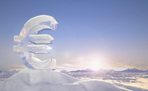 Frozen euro sign on top of mountain peak in snowy landscape at sunrise