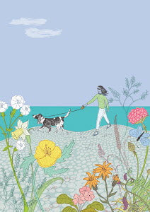Woman walking dog along beach among spring flowers