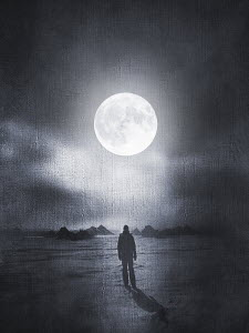 Man looking up at full moon in atmospheric landscape