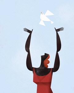 Happy woman releasing white bird