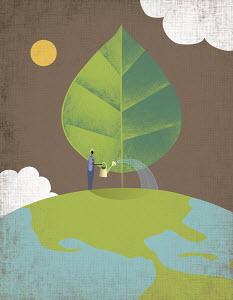 Man watering tree growing on top of globe