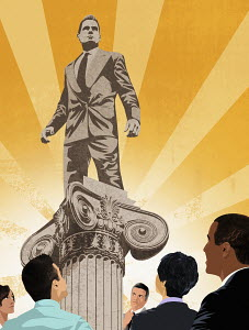 Colleagues admiring businessman standing on top of pedestal