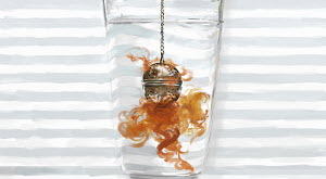Tea dispersing from infuser in glass of hot water