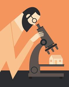 Man examining house under microscope
