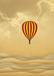 Hot air balloon flying over sand dunes