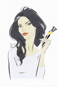 Beautiful woman looking at camera holding makeup brushes