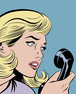 Close up of woman with stunned facial expression staring at telephone receiver