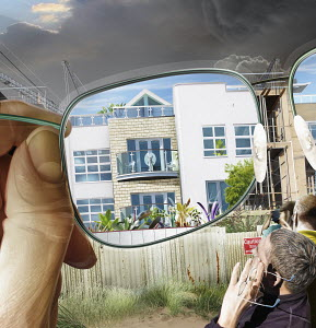 Man looking through glasses and imagining new building on construction site