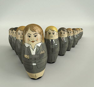 Businessmen nesting dolls lined up behind female boss