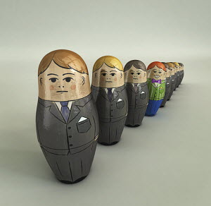 Smiling brightly dressed businessman standing out in row of serious nesting dolls