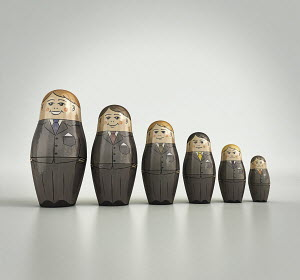 Businessmen nesting dolls in order of size and happiness