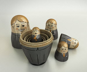 Small crying businessman revealed inside of open nesting dolls in order of size and happiness
