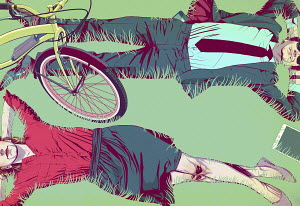 Couple taking a break lying down in grass beside bicycle, smart phone and digital tablet