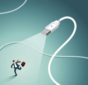 Businessman in spotlight running away from USB plug