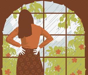 Woman looking at rain through window
