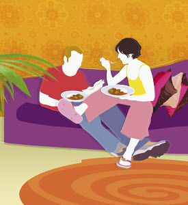Couple eating dinner in living room