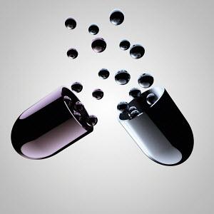 Spheres emerging from black metallic pill capsule