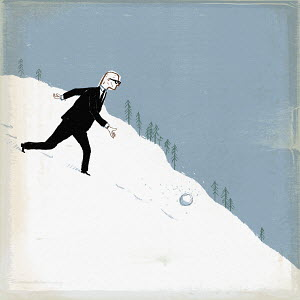 Businessman throwing snowball down hill