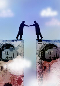 Businessmen shaking hands on a 10 Pound note