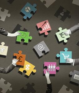Business people arranging jigsaw puzzle pieces with economic symbols