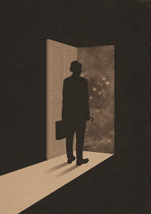 Businessman standing in open doorway of dark house looking out at starry night