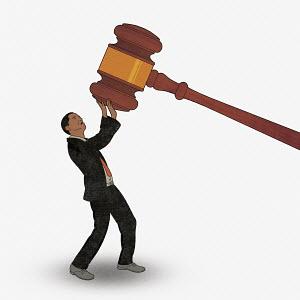 Businessman struggling under large gavel