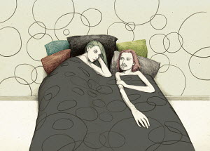 Couple lying in bed under dotted duvet