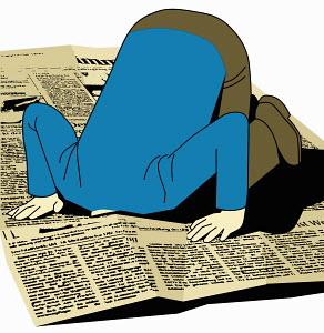 Kneeling man looking through newspaper