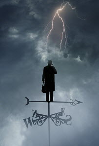 Man standing on weather vane in stormy weather