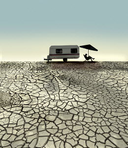 Man sitting on deckchair next to caravan on cracked soil