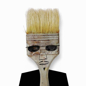 Face of a man wearing sunglasses on paintbrush