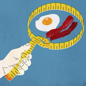 Hand holding tape measure around bacon and egg