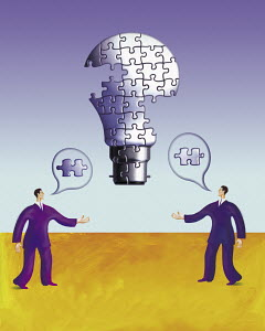 Two businessmen talking building up lightbulb made of puzzle pieces