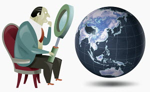 Businessman looking at globe with magnifying glass